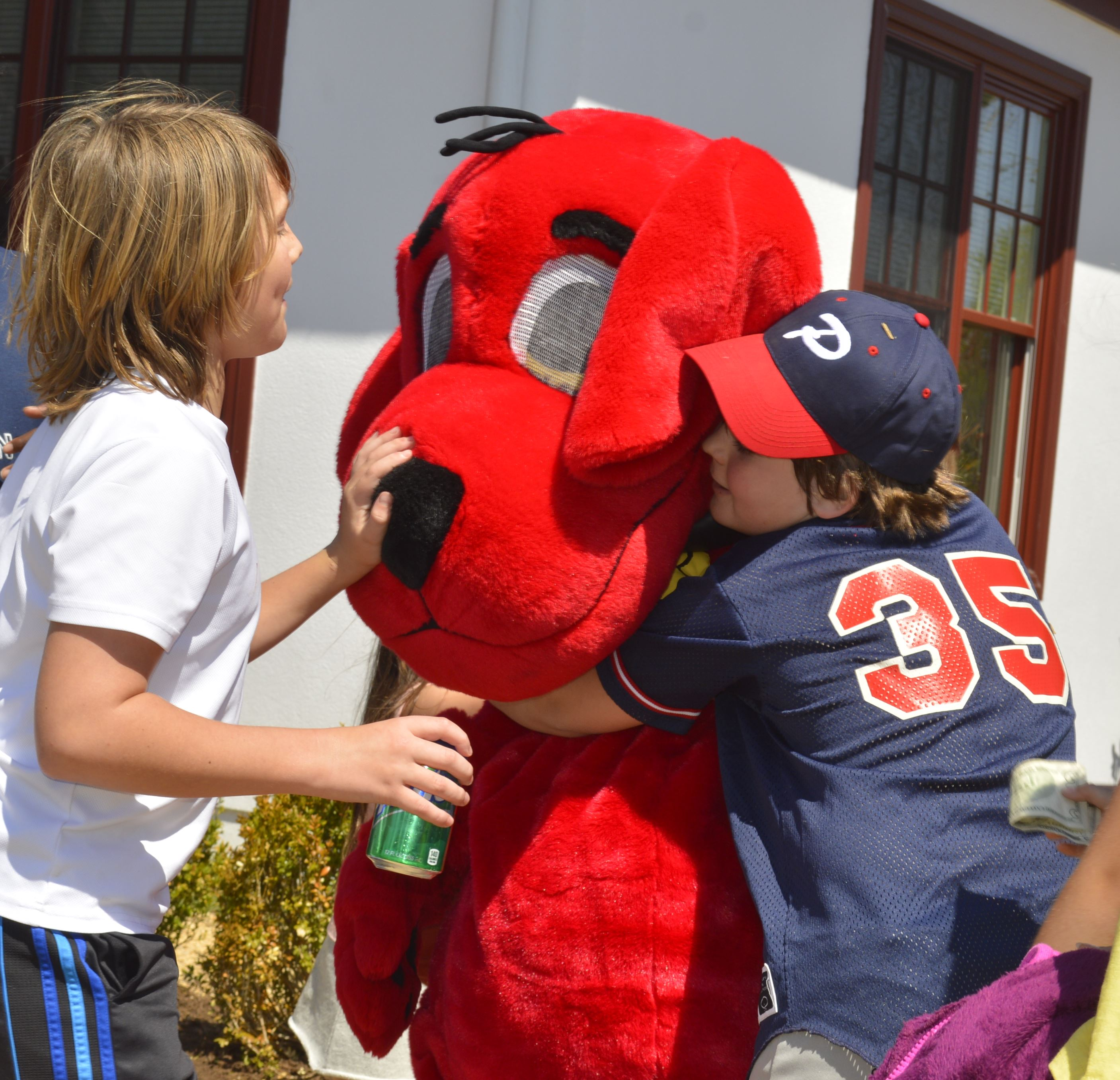 student hugging Clifford the Big Red Dog