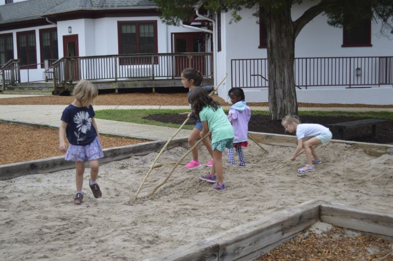 students playing in sandbox