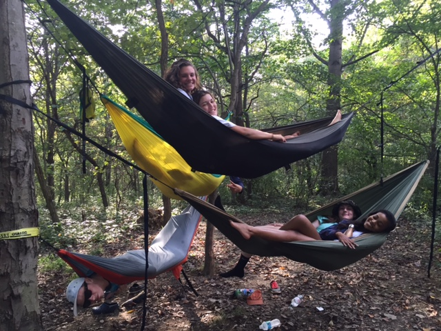 students relaxing in hammocks in woods